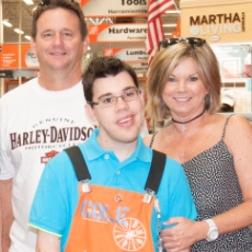 young man working at the home depot taking a picture with a couple behind him all smiling and looking at the camera