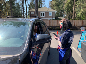 Customer at the drive-thru event for Bloomfest 2021, making a purchase from one of our volunteers.