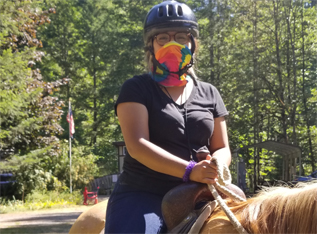 Young woman camper on a horse, wearing a helmet and a protective mask.