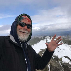 Connecting Communities participant, Gerardo B. He is on top of a snowy mountain, looking into the camera. He is smiling and waving his hand at the camera. He has sunglasses, a bandana, and a hooded sweatshirt on, and he has a gray beard.
