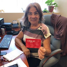 Connecting Communities Staff Member Magdalena P., holding a gift while smiling and sitting at her desk.
