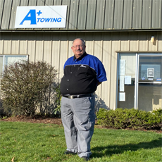 Tim Vaughn - an HVRP participant, posing and smiling in front of his new workplace at A+ Towing.