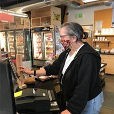 Senior woman, working as a cashier, wearing a protective mask.