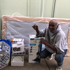 Veteran participant, Bennie Harris - with his move-in supplies and welcome-home kit, in his new apartment home.