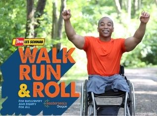 Man in wheelchair, wearing an orange shirt and gray shorts, raising his arms up and cheering. He is smiling, on a path, in a forest.