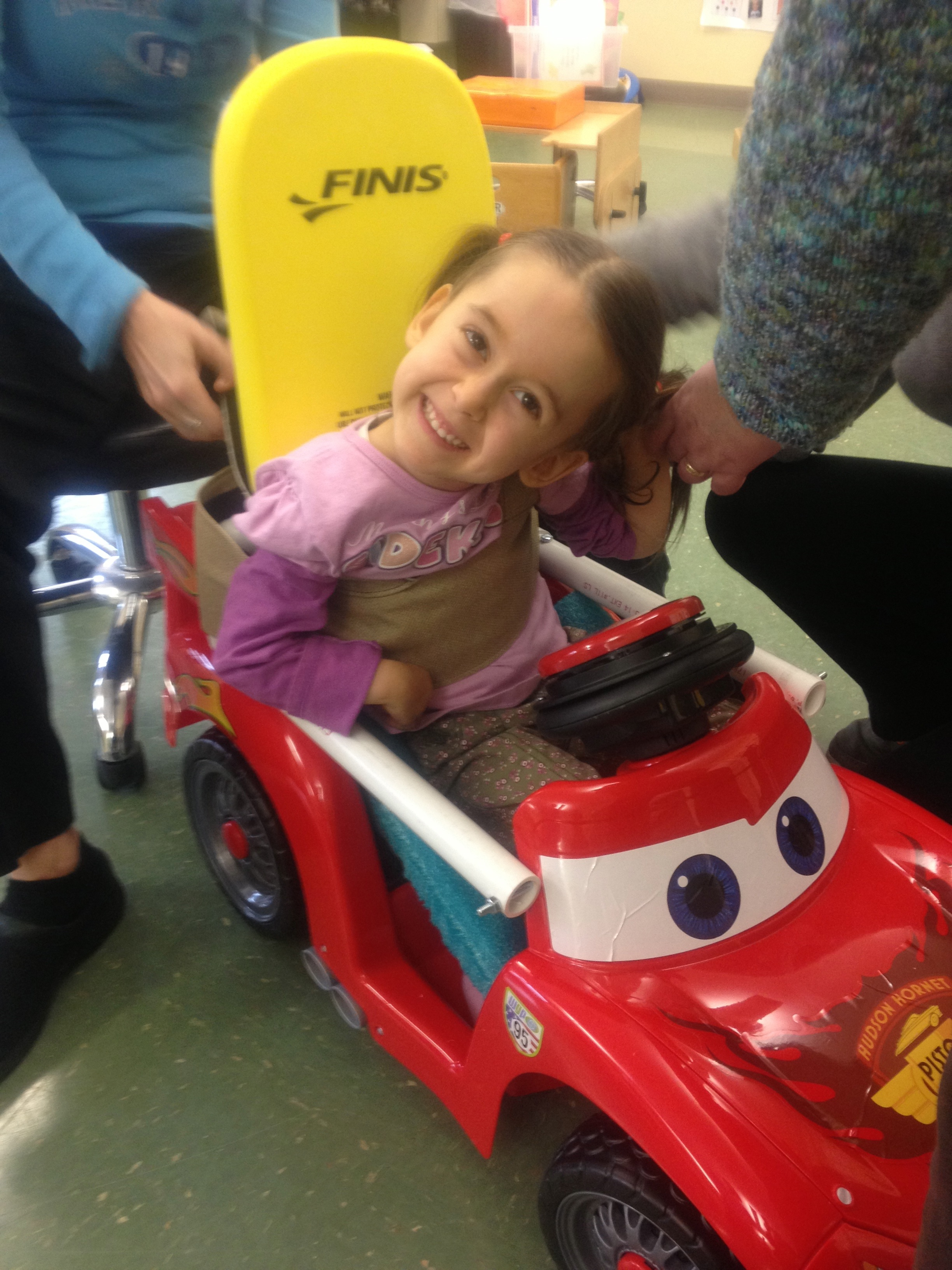 girl in adapted toy car