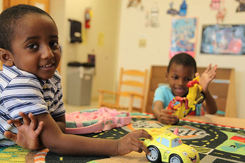 boys playing with cars at a table