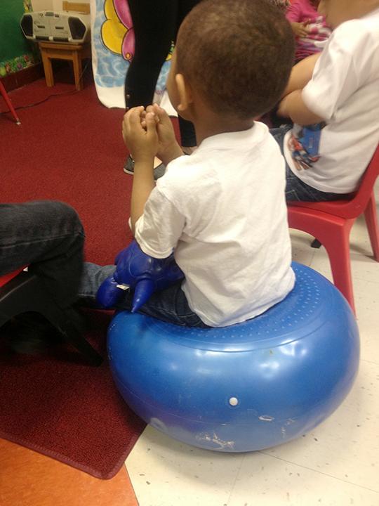 Boy sitting on movement cusion