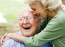 Elderly woman huggin elderly man