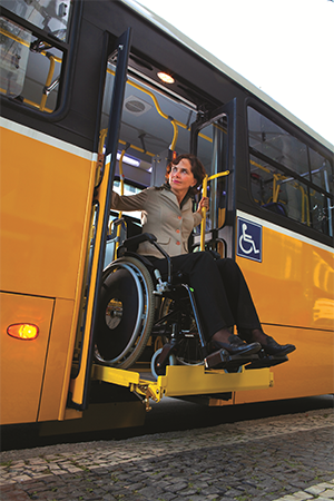 A woman in a wheelchair on a bus lift looking off to her right