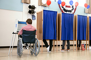 A man in a wheelchair at an accessible voting booth
