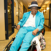 An elderly woman in a blue suit in a wheelchair