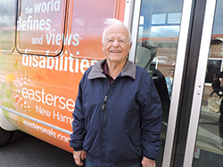 An elderly man standing next to an Easterseals transportation vehicle