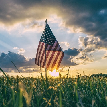 american flag in a field in front of a sunset