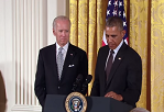 President Obama speaking at podium with VP Joe Biden standing behind him