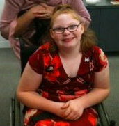 A preteen girl sits in a wheelchair smiling
