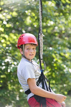 A young boy wearing a harness to rock climb