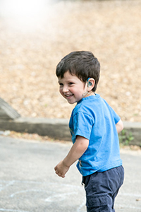 A young boy wearing a hearing aid looks to his left