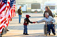 A veteran in a wheelchair with a young caregiver and a little boy