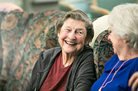 Two elderly women on a couch smiling at one another