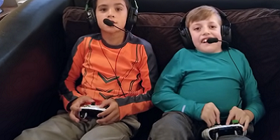 two kids, one with a physical disability, face the camera as they play a videogame with special controllers