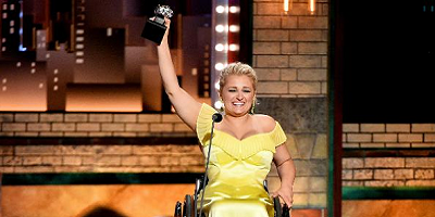 Ali lifts her tony award in the air as she gives a speech on stage in a wheelchair