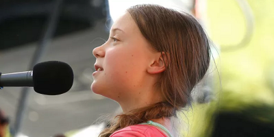 Greta, an activist with autism, speaks at a microphone