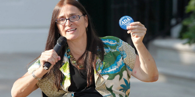 Disability advocate Marca Bristo holds up an ADA button while speaking into a microphone