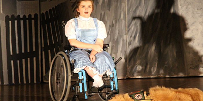 a young girl in a wheelchair is on stage stressed as dorthy from wiz of oz