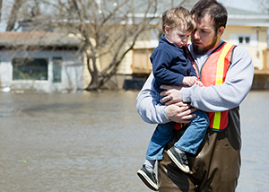 A rescue worker holding a young child