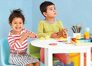 Two children at a table with colored pencils