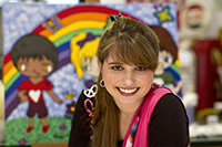 Haley Moss smiling in front of a mural featuring a rainbow in the background