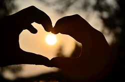 Two hands forming a heart in front of a sunset