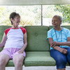 Two elderly women sitting outside on a porch swing