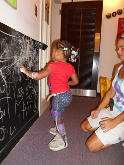 Jalea, a toddler, is standing using her assisitve devices,  playing with chalk