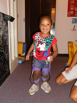 Jalea, a toddler, is standing using her assisitve devices, smiling