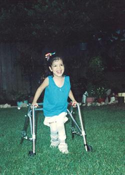 Kelley as a child, walking across a lawn using a walker