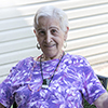 An elderly woman wearing a purple shirt smiling