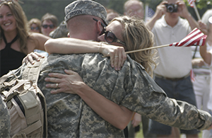 A woman hugging a soldier in uniform