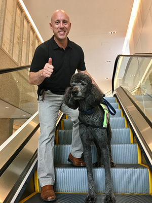 Tim and Colton, a poodle, on an escalator.