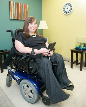 A woman in a wheelchair holding a tablet