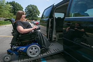 A woman in a wheelchair using a ramp to board a van