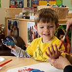 Donation Ad Photo of CDC Child handpainting