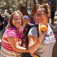 Camp 2018 Website Photo With Camper and Volunteer Waiving with an Orange