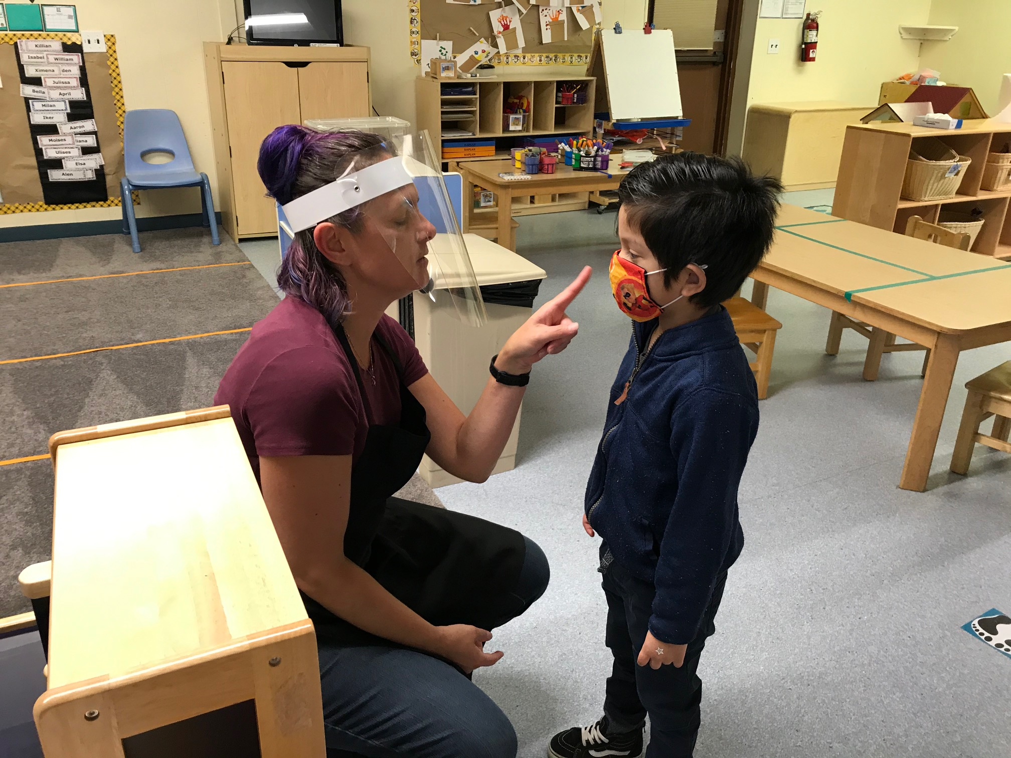 CDC IE opening teacher in PPE with kid