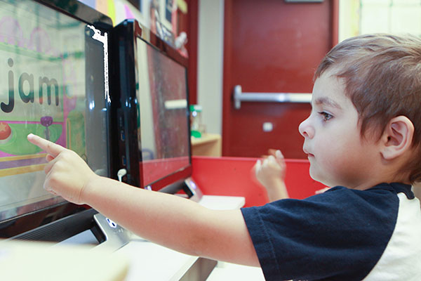 Kid pointing at word jam on computer screen
