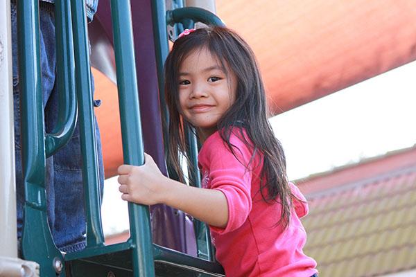 Asian pre-school girl on playground climbing equipment
