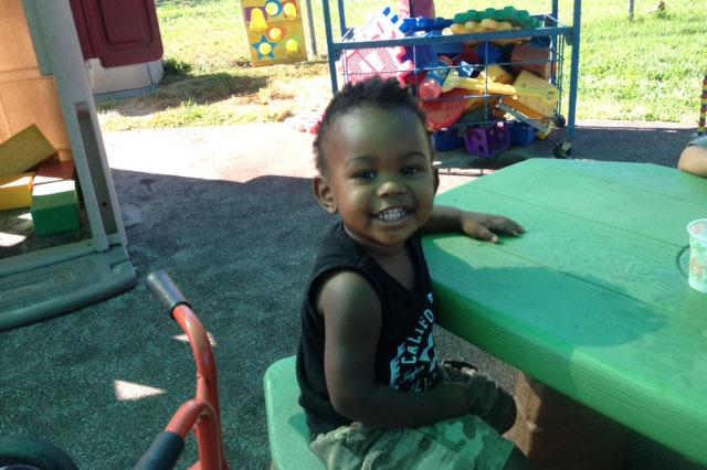 African American toddler smiling at camera