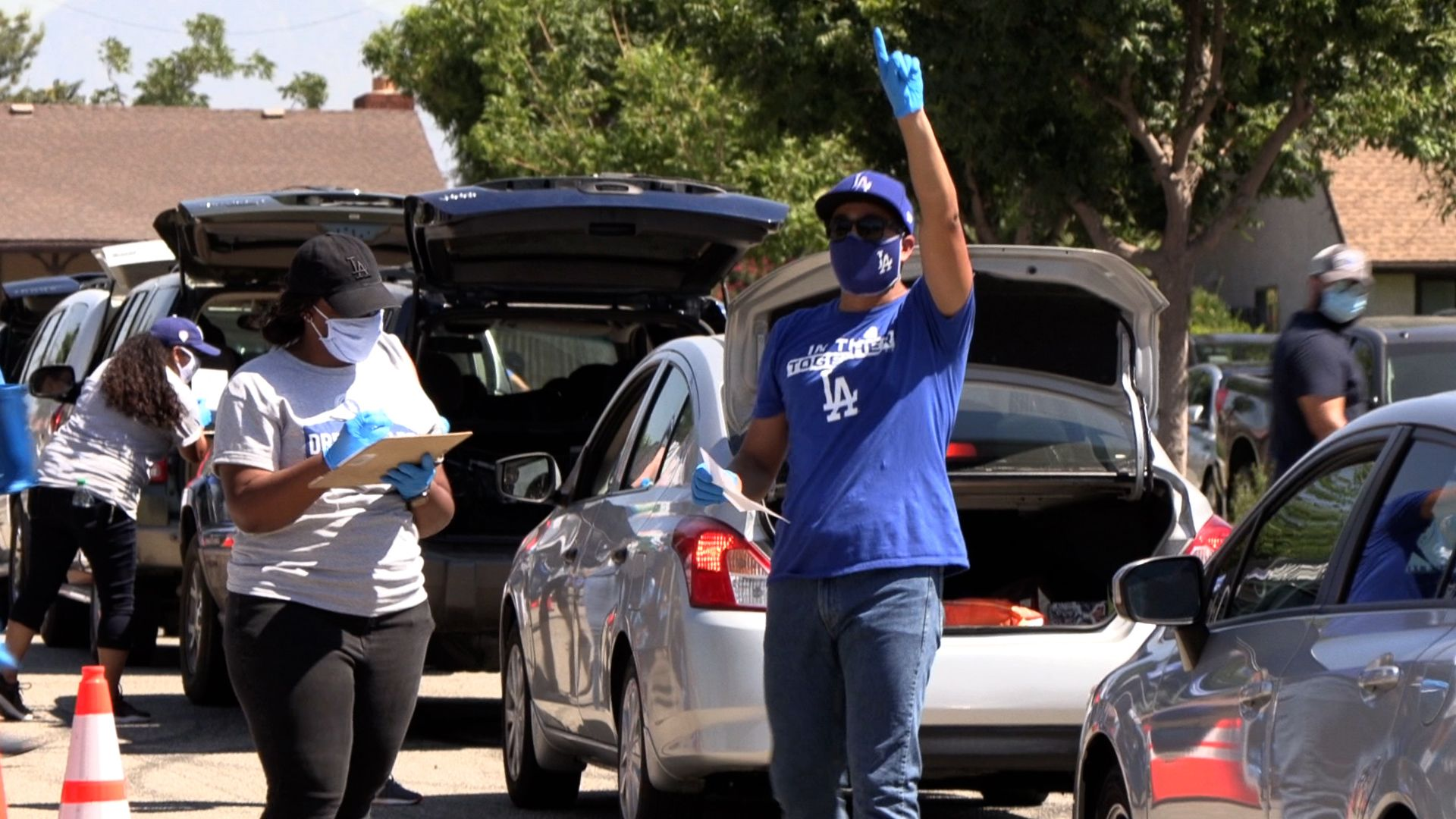 Volunteers at Dodgers Foundation food distribution event with line of cars