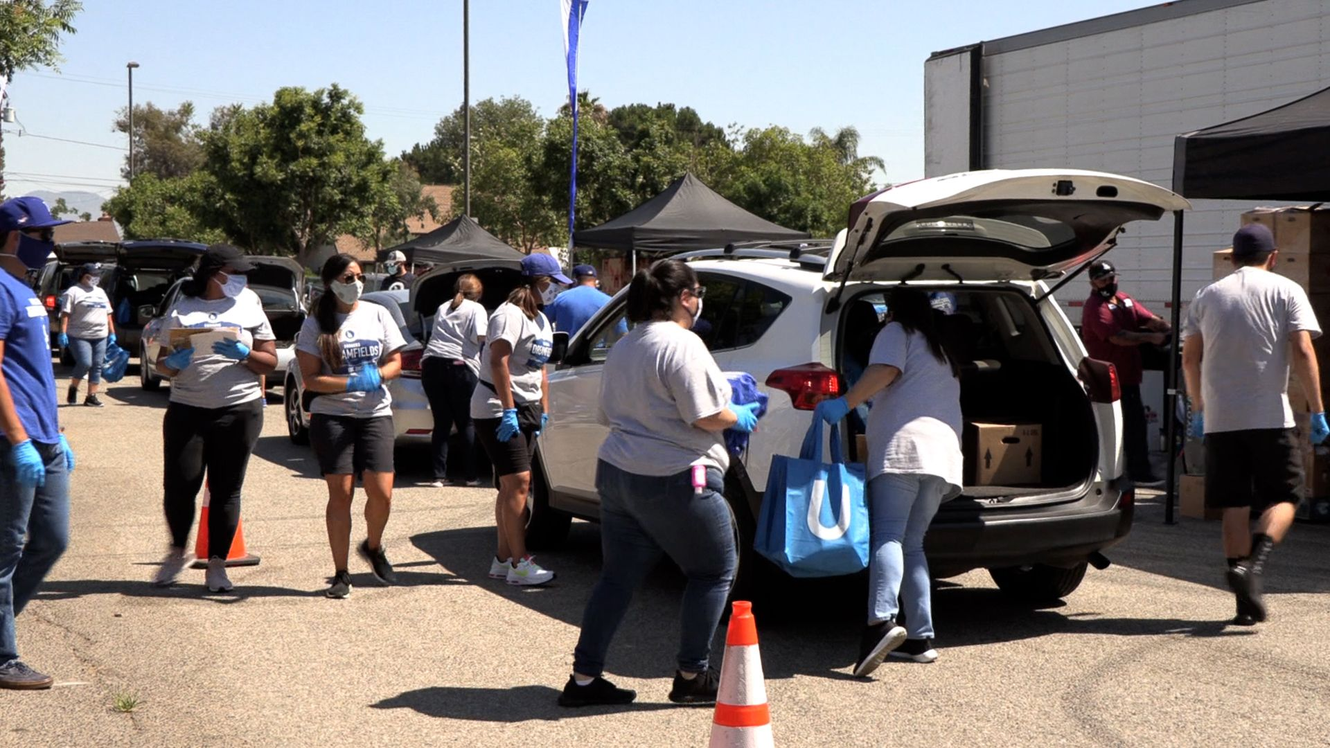 Volunteers at Dodgers Foundation food distribution event fill trunks with food